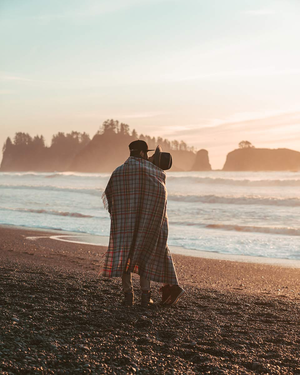 Girl and Boy wrapped in blanket on Rialto Beach