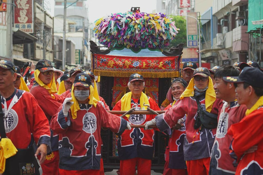 image of a group of people dressed in red carrying a palaquin