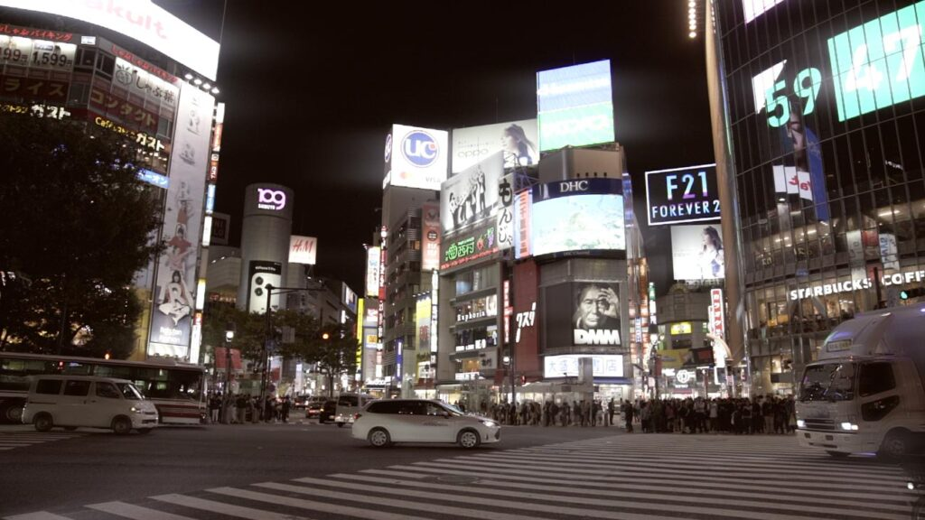 image of shibuya crossing at night with cars crossing the street