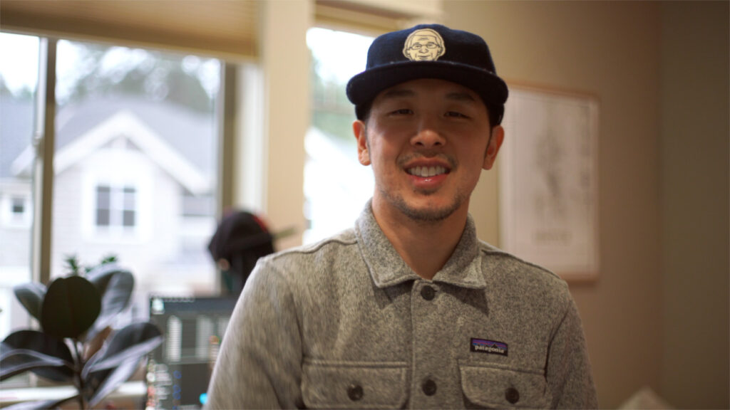 image of a man with a blue hat and gray shirt smiling towards camera