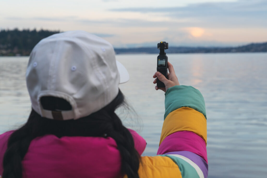 up close image of girl with white hat and colorful jacket using a dji pocket 2 camera