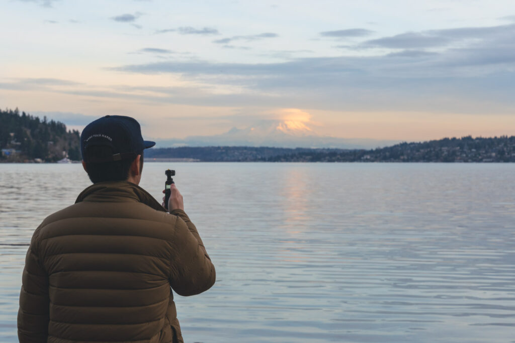 image of guy in green jacket and blue hat using the dji pocket 2 camera in front of a body of water
