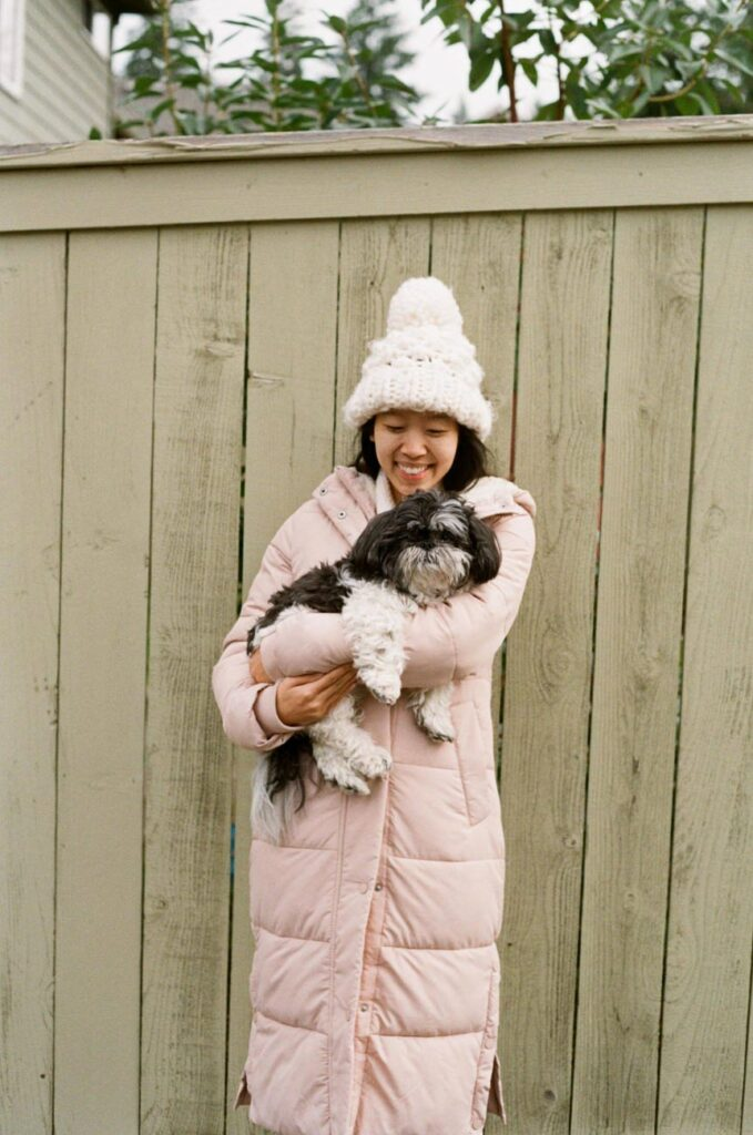 image of girl in pink jacket with shih tzu in arms in front of fence
