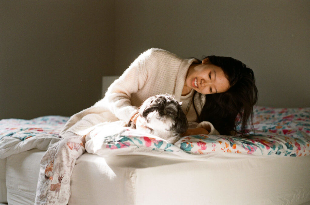 image of girl sitting on bed in sun with shih tzu