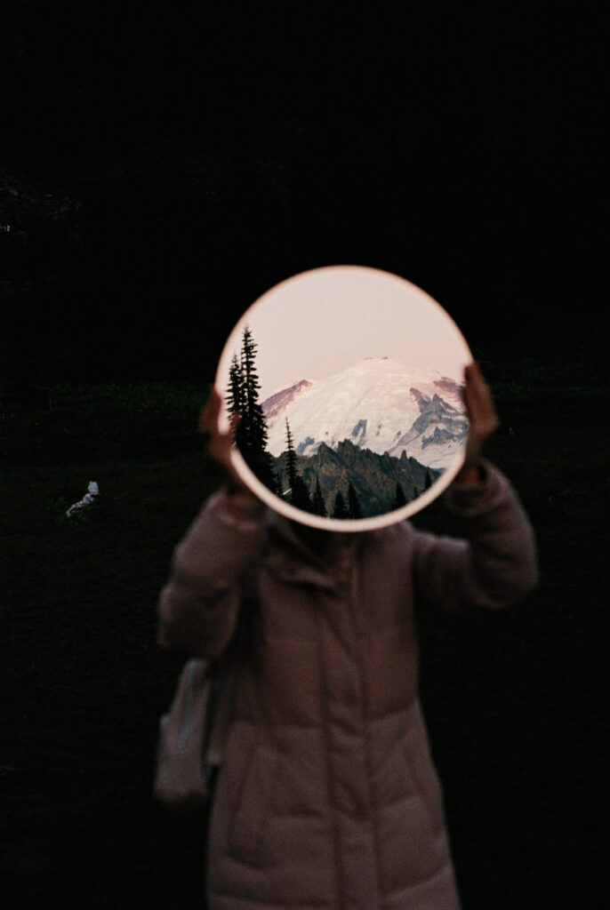 image of a girl holding up a mirror with mount rainier reflection in the mirror