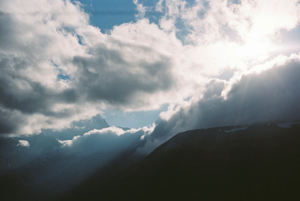 image of mountain range with clouds and the sun shining through