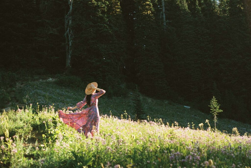 image of girl in pink dress with hat in field of grass lit up by sunlight