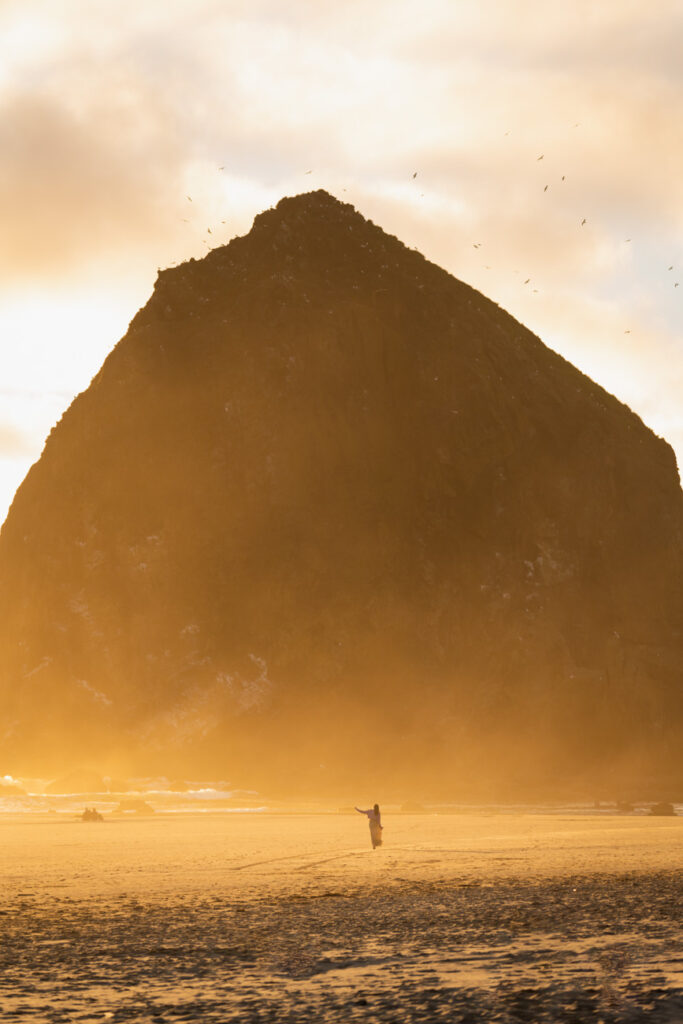 image of a girl in front of cannon beach haystack with orange sunset glow