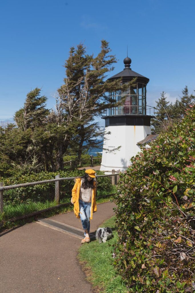 image of girl and a dog in front of cape meares lighthouse