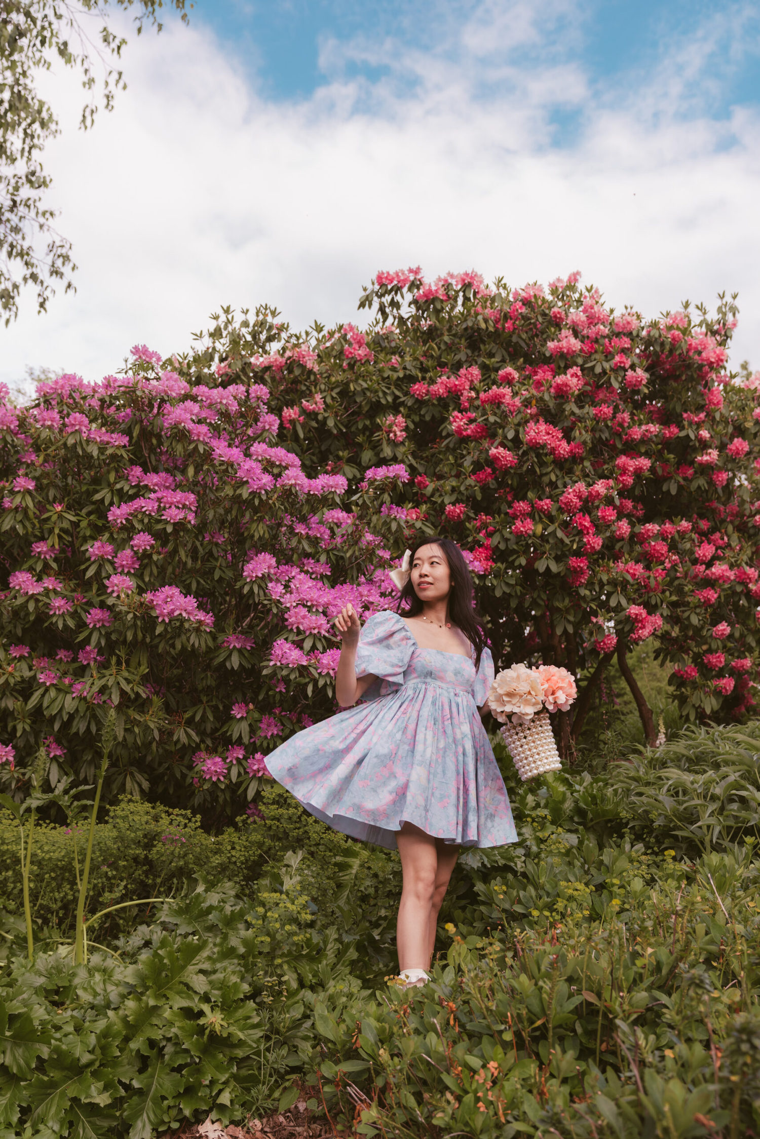 Girl with pastel dress in front of rhododendron flowers