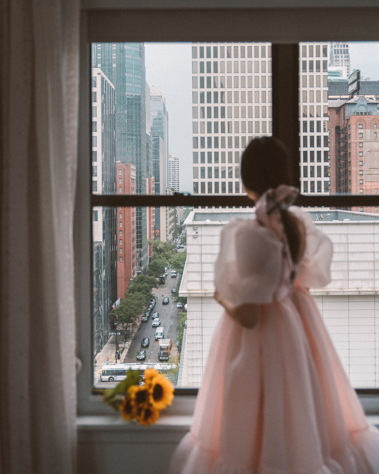 Girl in pink dress looking out hotel window in Chicago
